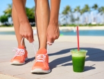 Running woman runner with green vegetable smoothie.  Fitness and healthy lifestyle concept with fema